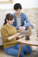 タブレットPCを見ているカップル 07800057585| 写真素材・ストックフォト・画像・イラスト素材|アマナイメージズ