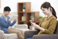 スマートフォンを操作する女性 07800057587| 写真素材・ストックフォト・画像・イラスト素材|アマナイメージズ