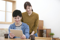タブレットPCを見ているカップル 07800057632| 写真素材・ストックフォト・画像・イラスト素材|アマナイメージズ