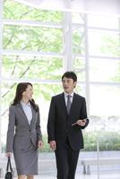 会話するビジネスマンとビジネスウーマン 07800057713| 写真素材・ストックフォト・画像・イラスト素材|アマナイメージズ