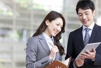 タブレットPCを見ている笑顔のビジネスマンとビジネスウーマン 07800057722| 写真素材・ストックフォト・画像・イラスト素材|アマナイメージズ