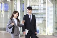 スマートフォンを見ている笑顔のビジネスマンとビジネスウーマン 07800057734| 写真素材・ストックフォト・画像・イラスト素材|アマナイメージズ