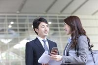 会話するビジネスマンとビジネスウーマン 07800057737| 写真素材・ストックフォト・画像・イラスト素材|アマナイメージズ