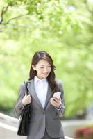スマートフォンを見ているビジネスウーマン 07800057768| 写真素材・ストックフォト・画像・イラスト素材|アマナイメージズ