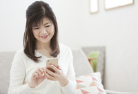 スマートフォンを操作する中年女性