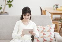 ソファーでタブレットPCをする中年女性