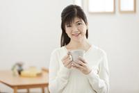 ティーカップを持つ中年女性