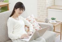 ソファーでパソコンをする中年女性