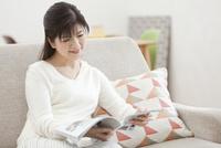 ソファーで読書をする中年女性