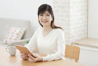 テーブルでタブレットPCを手にする中年女性