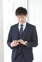 スマートフォンを操作するビジネスマン 07800058095| 写真素材・ストックフォト・画像・イラスト素材|アマナイメージズ