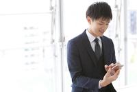 スマートフォンを操作するビジネスマン 07800058115| 写真素材・ストックフォト・画像・イラスト素材|アマナイメージズ