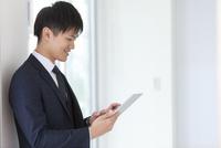タブレットPCを操作するビジネスマン 07800058116| 写真素材・ストックフォト・画像・イラスト素材|アマナイメージズ