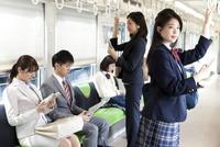 電車移動している男女 07800058125| 写真素材・ストックフォト・画像・イラスト素材|アマナイメージズ