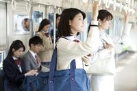 電車移動している男女 07800058126| 写真素材・ストックフォト・画像・イラスト素材|アマナイメージズ