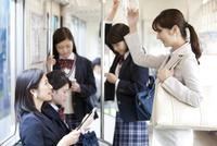 電車移動しているビジネスウーマンと女子高生 07800058135| 写真素材・ストックフォト・画像・イラスト素材|アマナイメージズ