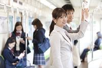 電車移動している男女 07800058137| 写真素材・ストックフォト・画像・イラスト素材|アマナイメージズ