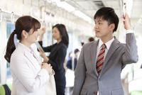 通勤電車に乗るビジネスマンとビジネスウーマン 07800058138| 写真素材・ストックフォト・画像・イラスト素材|アマナイメージズ