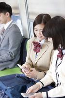 電車に乗る女子高生とビジネスマン 07800058149  写真素材・ストックフォト・画像・イラスト素材 アマナイメージズ