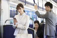 通勤電車に乗るビジネスマンとビジネスウーマン 07800058154| 写真素材・ストックフォト・画像・イラスト素材|アマナイメージズ