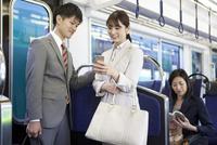 通勤電車に乗るビジネスマンとビジネスウーマン 07800058155| 写真素材・ストックフォト・画像・イラスト素材|アマナイメージズ