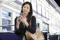 通勤電車でスマートフォンを操作するビジネスウーマン 07800058160| 写真素材・ストックフォト・画像・イラスト素材|アマナイメージズ