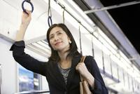 通勤電車に乗るビジネスウーマン 07800058161| 写真素材・ストックフォト・画像・イラスト素材|アマナイメージズ