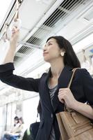 通勤電車に乗るビジネスウーマン 07800058162| 写真素材・ストックフォト・画像・イラスト素材|アマナイメージズ