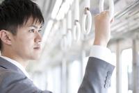 通勤電車に乗るビジネスマン 07800058165| 写真素材・ストックフォト・画像・イラスト素材|アマナイメージズ