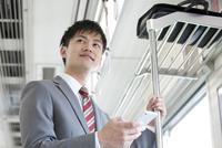 通勤電車に乗るビジネスマン 07800058168| 写真素材・ストックフォト・画像・イラスト素材|アマナイメージズ