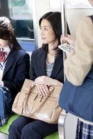 電車に乗るビジネスウーマンと女子高生 07800058187  写真素材・ストックフォト・画像・イラスト素材 アマナイメージズ