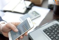 スマートフォンを持っているビジネスマンの手元 07800058462| 写真素材・ストックフォト・画像・イラスト素材|アマナイメージズ