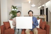 メッセージボードを持つ中高年夫婦