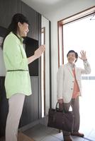 出勤する男性と見送る女性