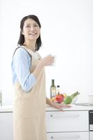 カップを持ってキッチンに立つ女性