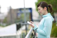 ジョギング姿でスマートフォンを持つ女性