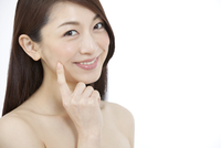 指で頬を触る女性