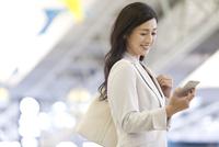 スマートフォンを見るビジネスウーマン 07900003100| 写真素材・ストックフォト・画像・イラスト素材|アマナイメージズ