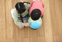 地球儀を見る姉と弟