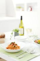 パスタとワイングラスが並ぶ食卓