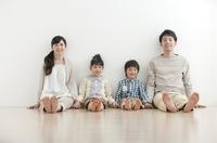 フローリングに座る家族4人