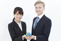地球をもつ外国人男性とビジネスウーマン