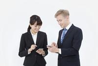 スマートフォンを操作する外国人男性とビジネスウーマン