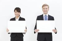 メッセージボードを持つ外国人男性とビジネスウーマン