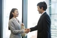 握手をするビジネスマンとビジネスウーマン