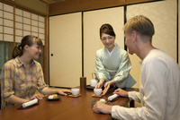 お茶を差し出す日本人女性と外国人カップル