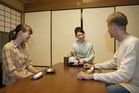 お茶を注ぐ日本人女性と外国人カップル