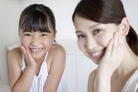 手を頬に当てる母娘 07900006189| 写真素材・ストックフォト・画像・イラスト素材|アマナイメージズ