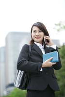スマートフォンで話すビジネスウーマン 07900006224| 写真素材・ストックフォト・画像・イラスト素材|アマナイメージズ