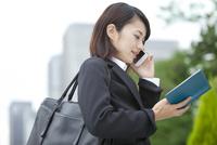 スマートフォンで話すビジネスウーマン 07900006267| 写真素材・ストックフォト・画像・イラスト素材|アマナイメージズ